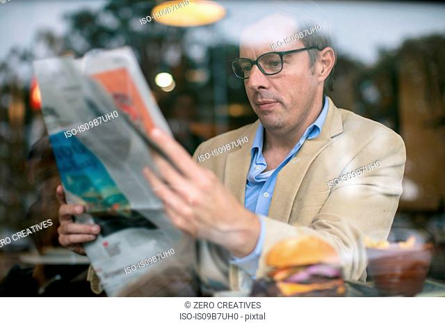 Man in coffee shop reading newspaper
