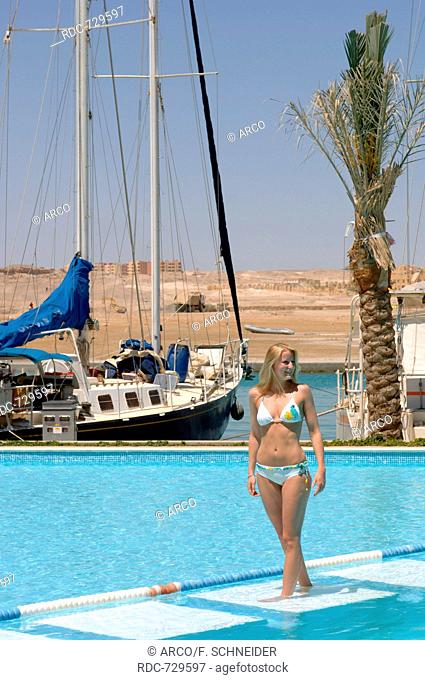 Young woman at poolside, Port Ghalib, Egypt, Africa
