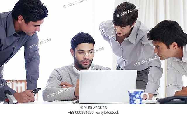 Group of businesspeople gathered around a laptop and having a serious discussion