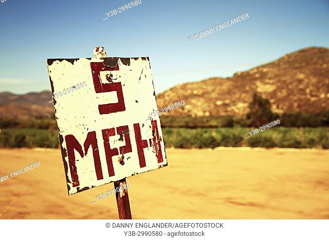 Rusty, old speed limit sign in the desert with mountains in the background