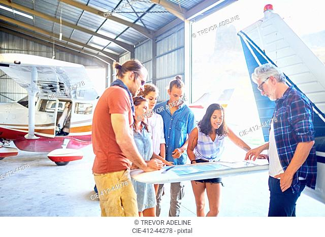 Friends planning trip at map in airplane hangar