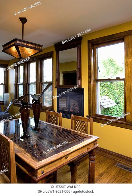 EATING AREA: breakfast room, gas fireplace in wall under mirror, antique East Indian door recycled as a table top, yellow walls