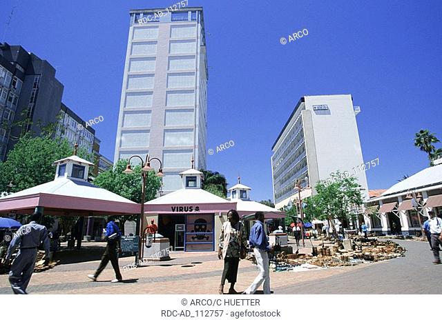Stall with wood carvings and tower blocks at Independence Avenue Windhoek Namibia