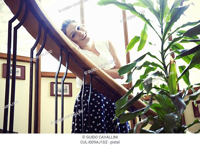 Portrait of young woman in vintage clothes leaning on banister