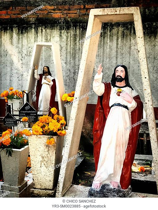 Images of the Sacred Heart of Jesus Christ decorate tombs during Day of the Dead celebrations in Mexico City, Mexico