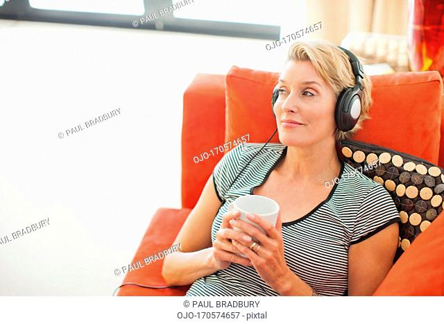 Woman drinking coffee and listening to headphones