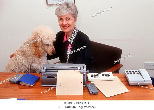 Woman with visual impairment sitting at desk in front of Braille typewriter stroking guide dog