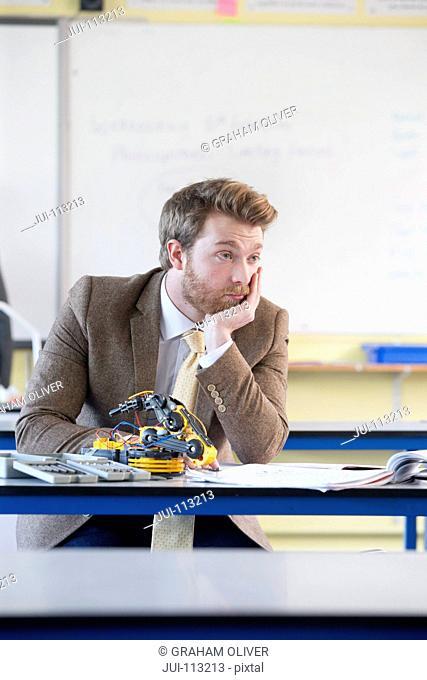 Bored teacher assembling robot in science class