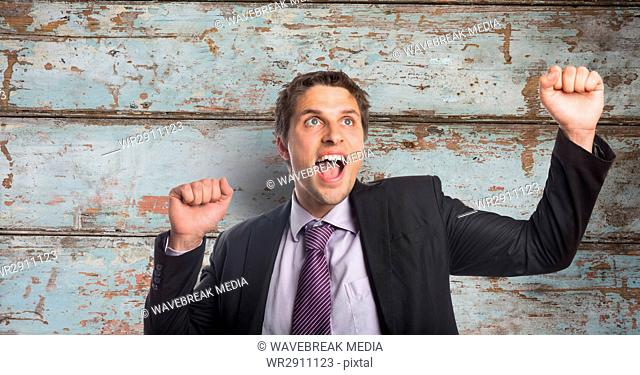Happy businessman celebrating success against wooden wall