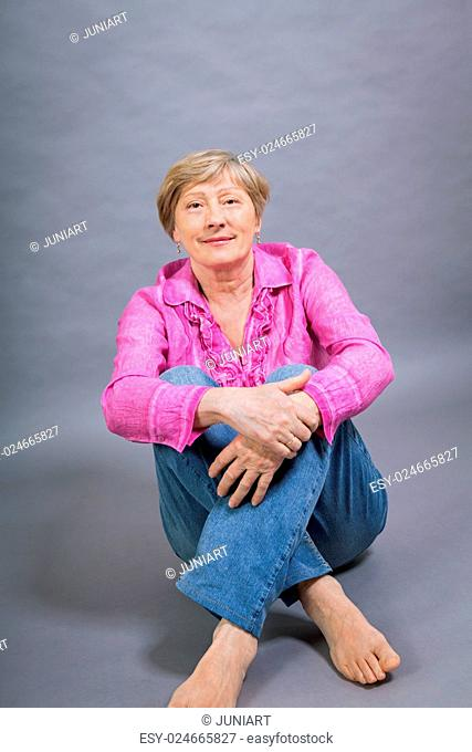 Beautiful blond trendy senior woman posing in a pink blouse and jeans sitting on the floor clasping her knee and smiling at the camera, on grey