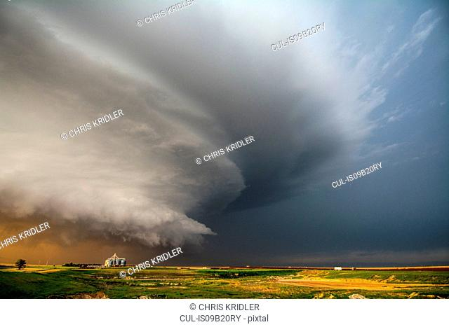 A tornado-producing supercell thunderstorm spinning over ranch land at sunset near Leoti, Kansas