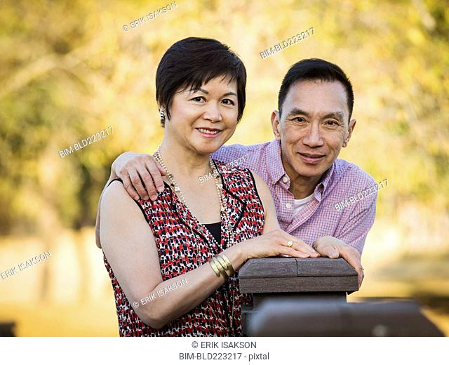 Older Chinese couple smiling outdoors