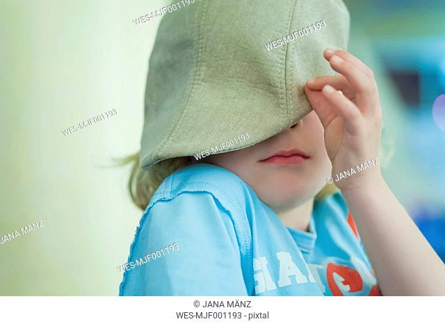 Blond hiding his face with a cap