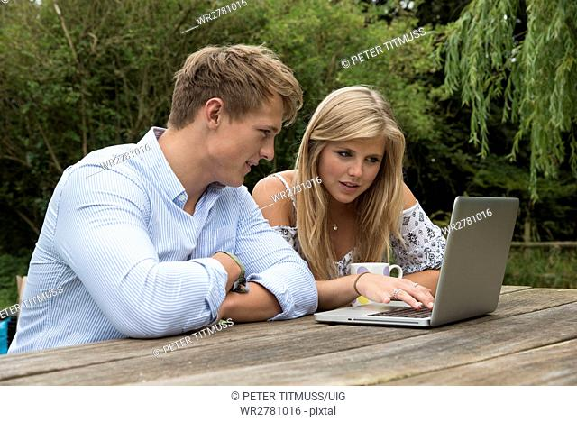 Teenage couple using a computer on a garden table