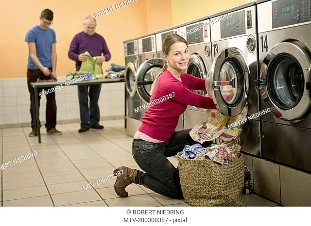 Young woman filling up cloths in washing machine while men in background