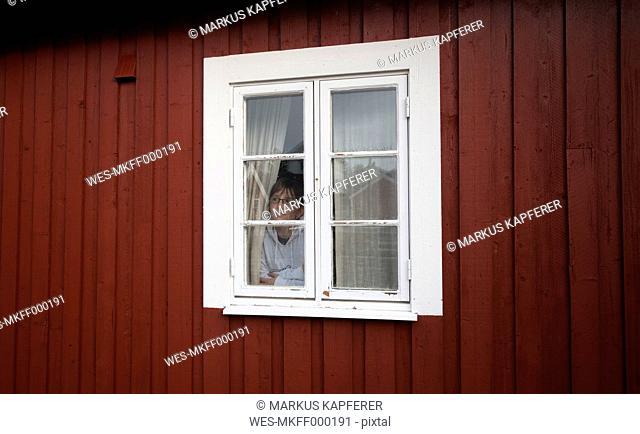 Norway, Lofoten, woman looking through window