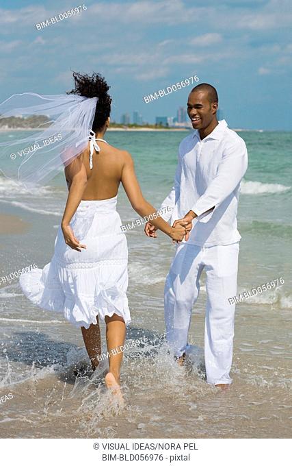 Multi-ethnic bride and groom walking in ocean surf