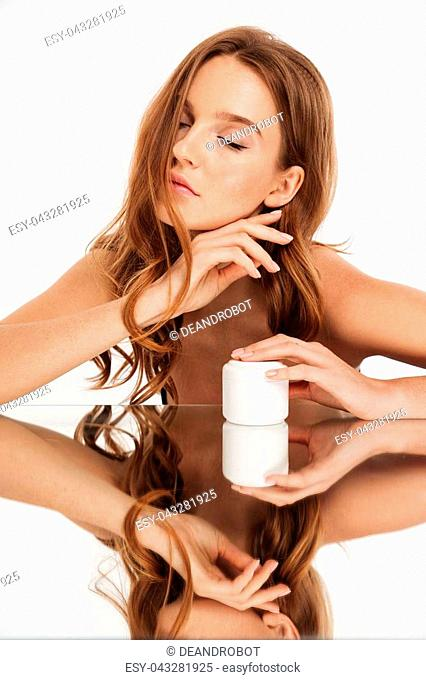 Vertical Beauty portrait of ginger woman with long hair and closed eye sitting by the mirror table with body cream over grey background