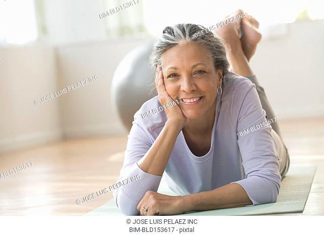 Older Hispanic woman laying on exercise mat