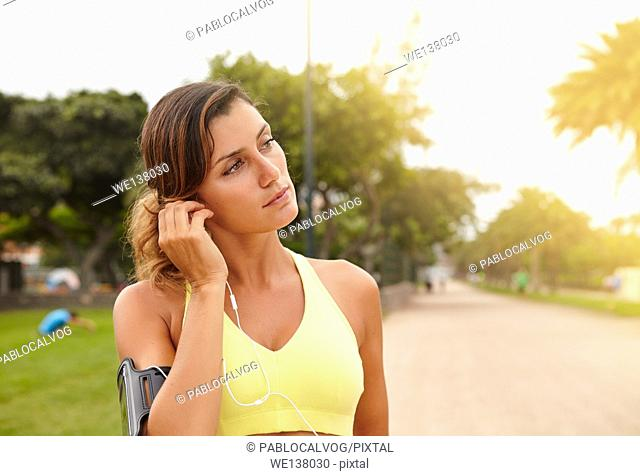 Young jogger in tank top listening to music while standing outside