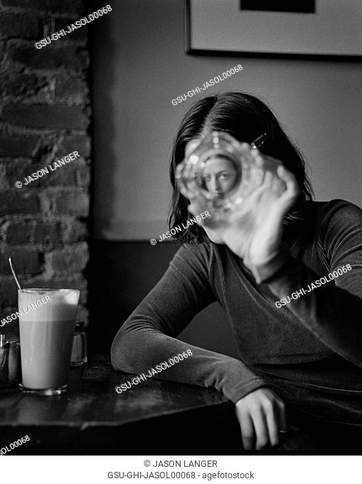 Woman in Café Looking Through Glass Ashtray