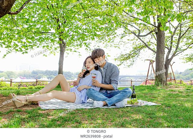 Young smiling couple having date at park in spring