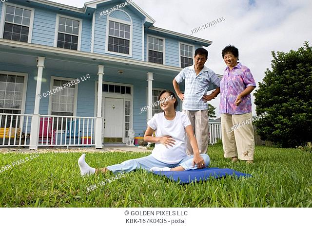 Pregnant woman sitting on mat and laughing while her parents stand by and watch