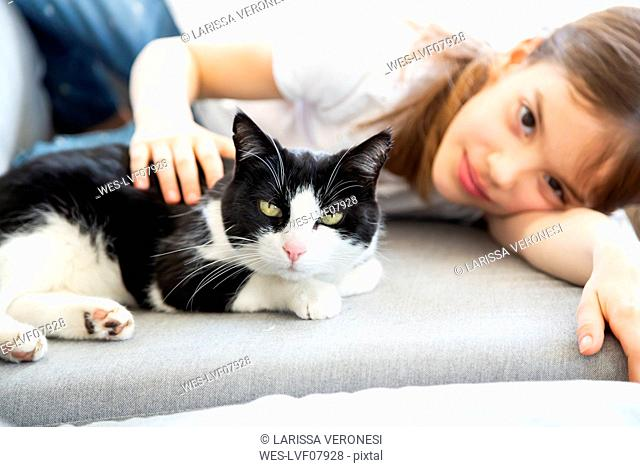 Little girl lying on couch with cat