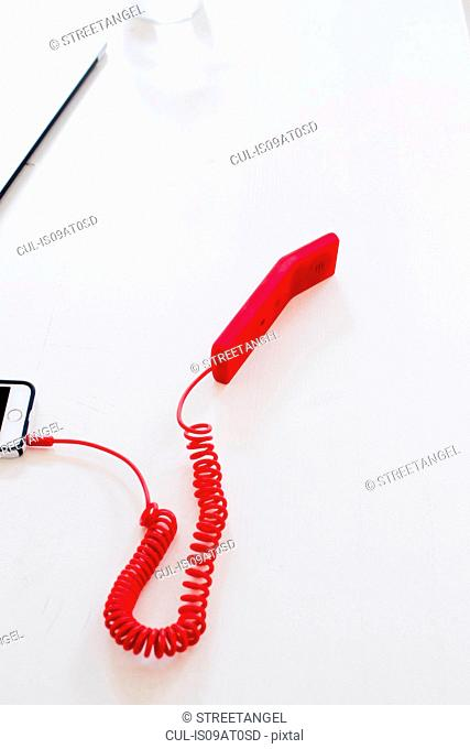 High angle view of red handset attached to smartphone