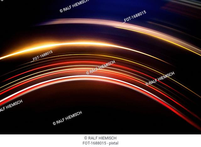 Full frame abstract image of vibrant light trails against black background