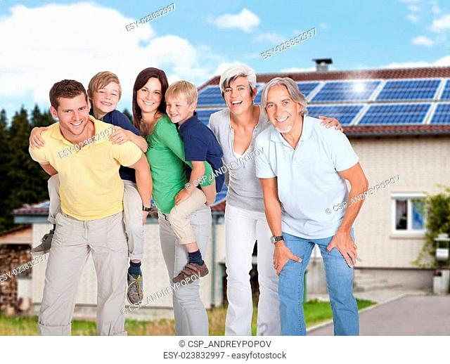 Multi Generation Family Standing Against House