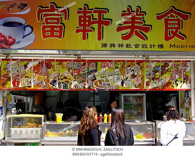 Women at a foodstall with a chinese Menu, China, Hong Kong