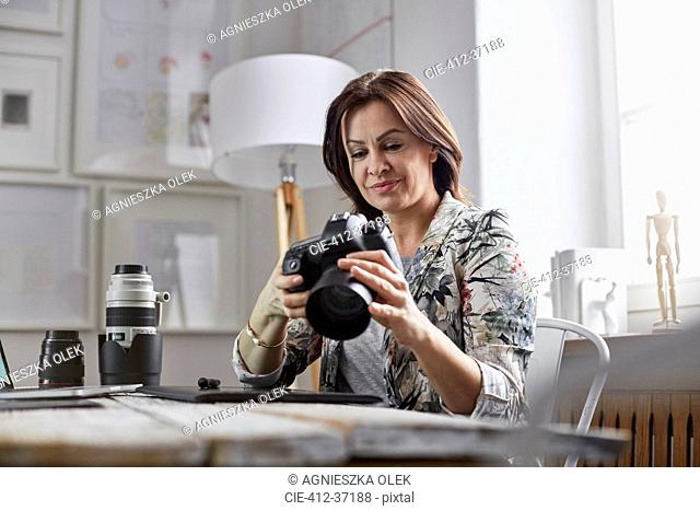 Female photographer using digital camera in office