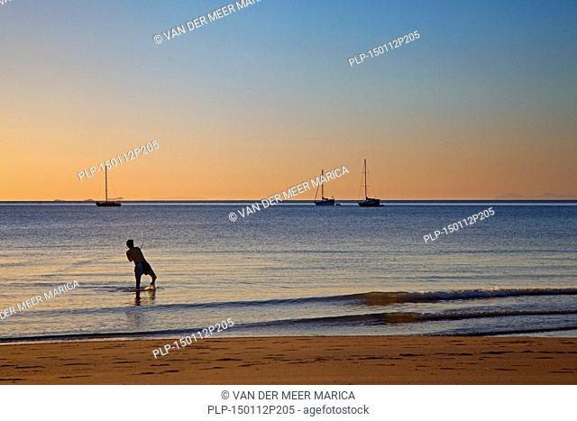 Sailing boats at sunset and sea angler fishing from the beach at Horseshoe Bay on Magnetic Island along the Coral Sea, north-eastern coast of Queensland