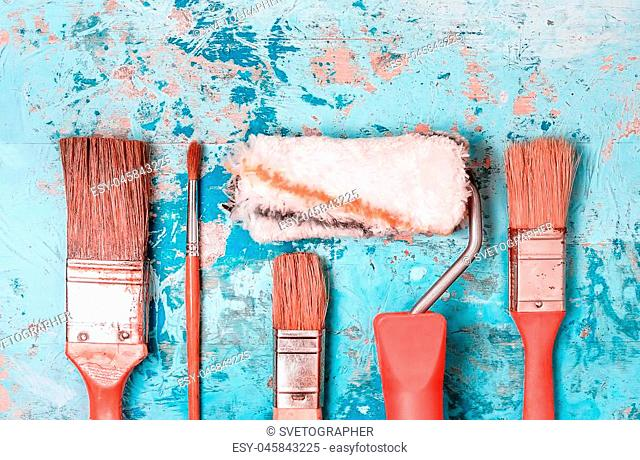 Set of painting brushes and rollers with red handles on a rustic wooden blue painted background