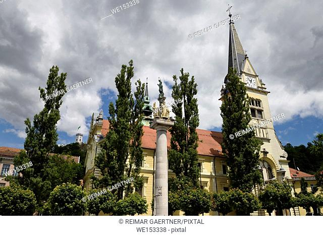 St James parish Catholic church and St. Mary's Column of the virgin in brass and stone statues of saints Ljubljana Slovenia with tower on Castle Hill