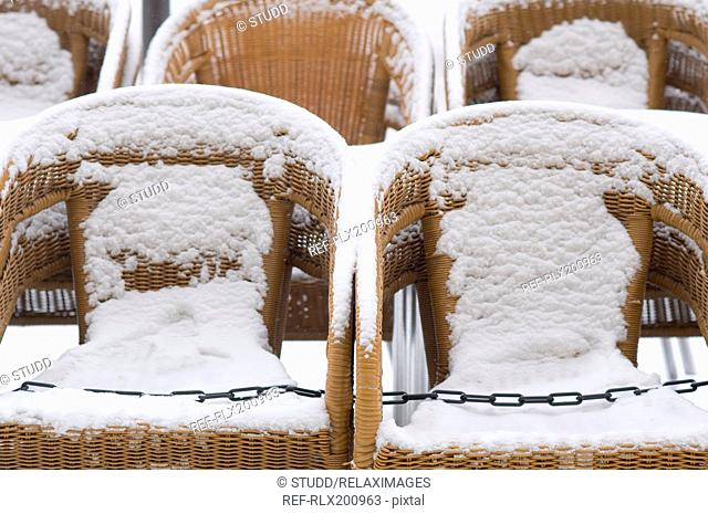 Row of snow covered wicker chairs