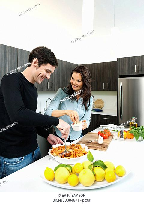 Couple making dinner together in kitchen