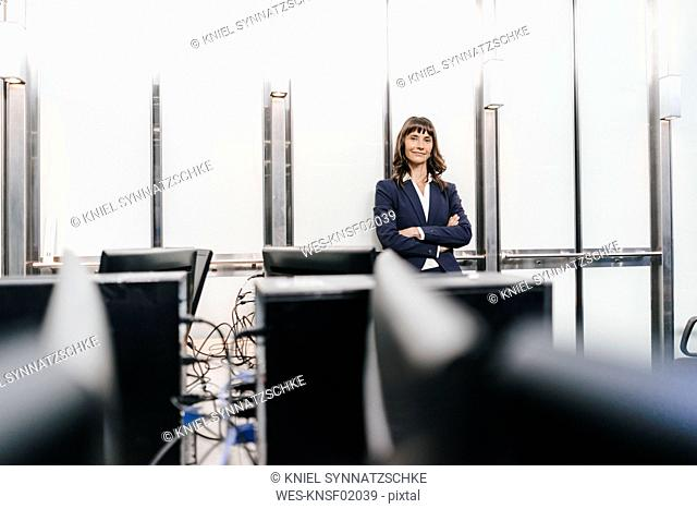 Successful businesswoman standing in office with arms crossed