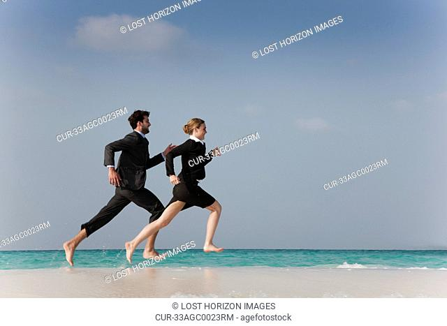 Business people running on beach