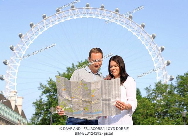 Couple reading map by London Eye ferris wheel, London, United Kingdom