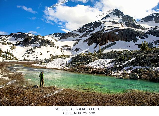 A man stands on the side of a river and looks up at Locomotive Mountain. This is a popular area for backpacking due to its beautiful views and relatively easy...