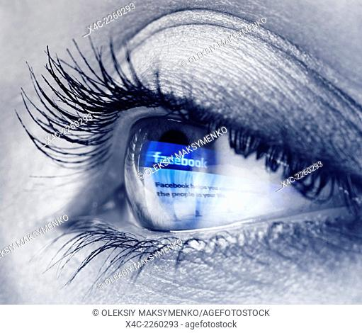 Closeup of a young woman blue eye with Facebook logo reflecting in it. Black and white with blue