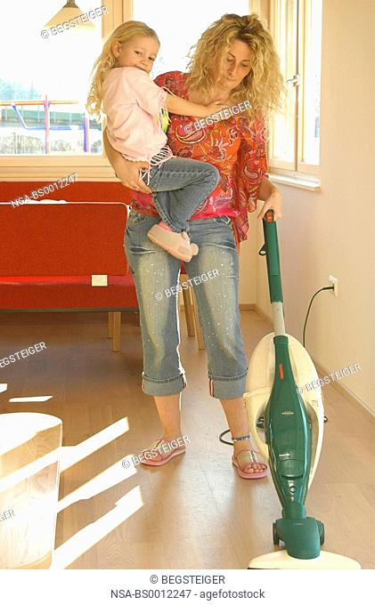 mother with daughter do the hoovering