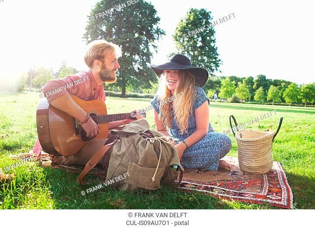 Romantic young couple playing acoustic guitar in park