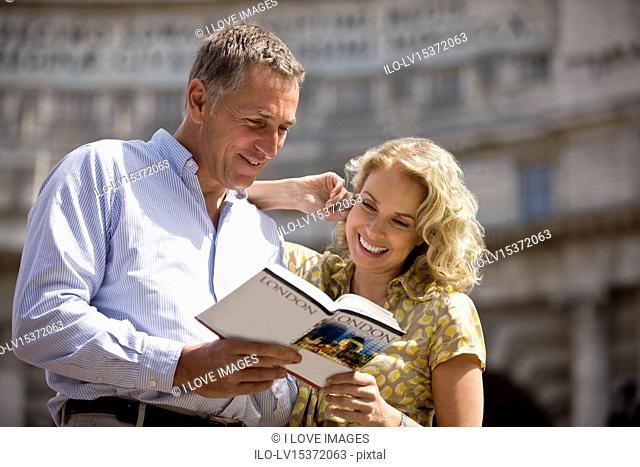 A middle-aged couple standing in front of Admiralty Arch, looking at a guidebook