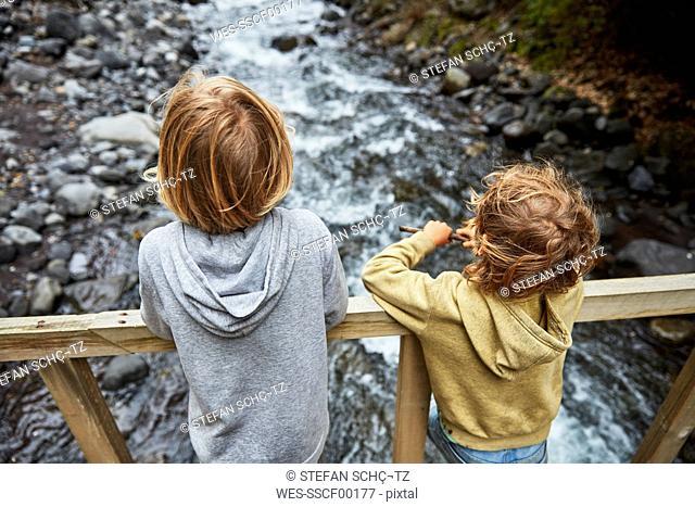 Chile, Patagonia, Osorno Volcano, Las Cascadas waterfall, two boys standing on bridge above a river