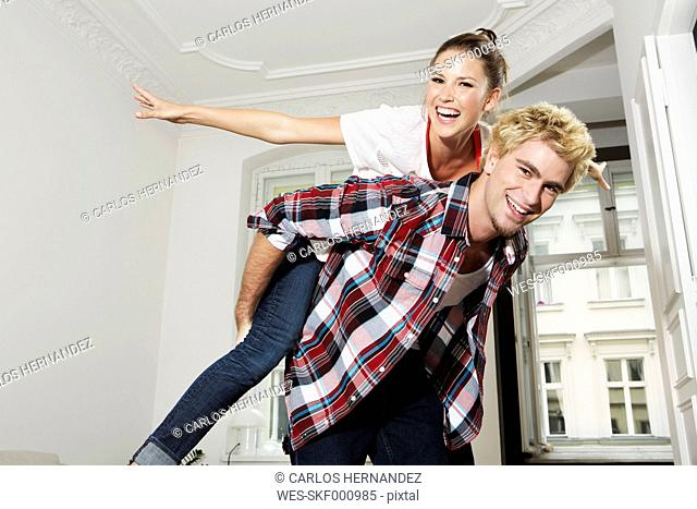 Germany, Berlin, Young man giving piggy back ride to woman