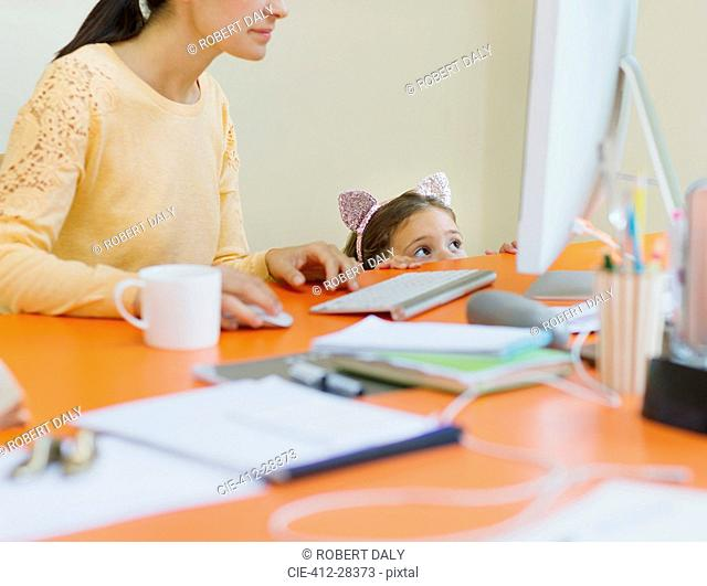 Girl in mouse ears headband watching mother work at computer