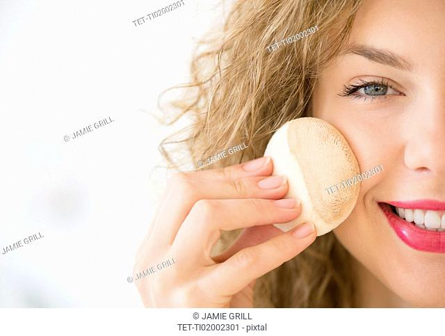 Young woman applying make up foundation